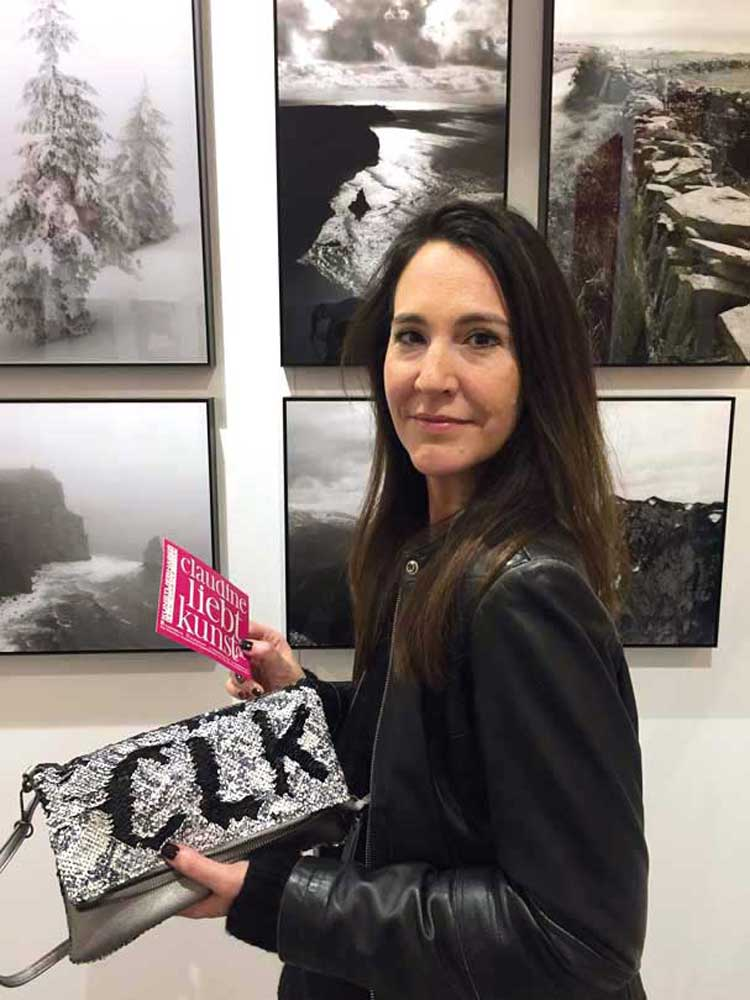 Claudine in ihrem Stand moreform.art vor Fotografien des Künstlers Emmanuel JULIEN / Immer mit dabei: die Lieblingstasche von myturnedlove.de
